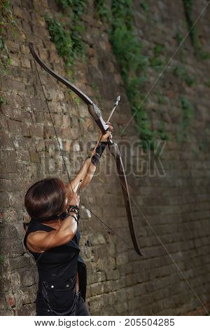 Athletic female warrior in black leather suite, shooting from bow. Incognito brunette woman with short hair, bronze sunburn, holding arrow and tacking focus at sky. Brick wall on background.