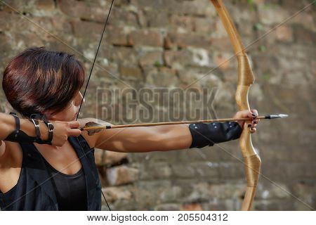 Back view of young confident brunette woman with short hair, wearing in black leather suite, shooting from bow. Female warrior holding arrow and tacking focus, looking away. Concept of warrior time.