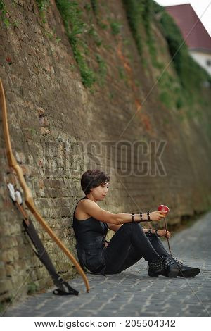 Young athletic woman in black leather suite, sitting on road, leaning on brick wall, near bow and arrow. Brunette girl with short hair resting after shooting from weapon. Old city.