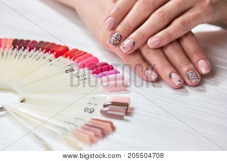 Female hands with nude manicure. Young woman hands with fresh beige manicure next to polish palette. Womens beauty and care.