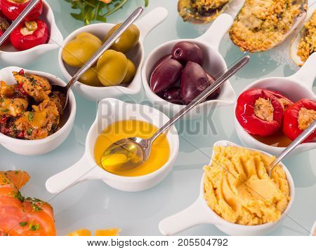 Snack set. Oktoberfest food frame concept. Variety of humus, olives, vegetables, cheese and sauces on white background. Top view