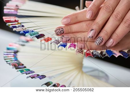 Caucasian woman beige patterned manicure. Female hands with beige manicure and black patterns on nails colors samples.