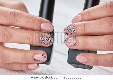 Perfect beige patterned manicure. Female manicured hands holding bottles with nail varnish. Fashion nail art studio.