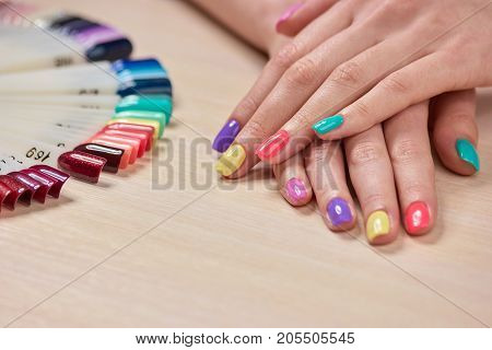 Girls stylish summer manicure. Caucasian woman hands with multicolored manicure on salon table. Summer brightful manicure.