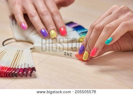 Female hand holding nails colors samples. Womans summer shellac nails. Choice summer fashion manicure.