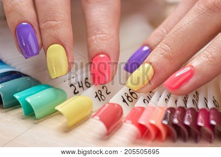 Beautiful summer manicure on female fingers. Womans fingers with bright varnished nails, nails samples variety. Professional salon of beauty and spa.