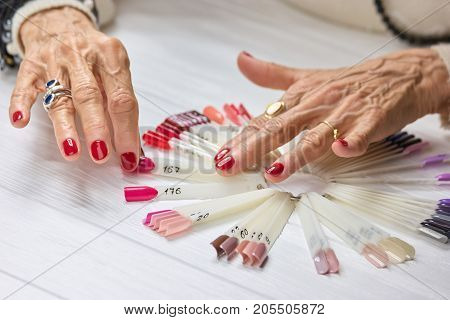 Senior womans hands with red manicure. Beautiful old woman hands with perfect red nails choosing summer pink nail sample.