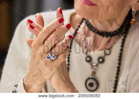 Senior woman luxury with manicure. Luxury old woman with red nails and elegant silver ring. Womens care and well-being.