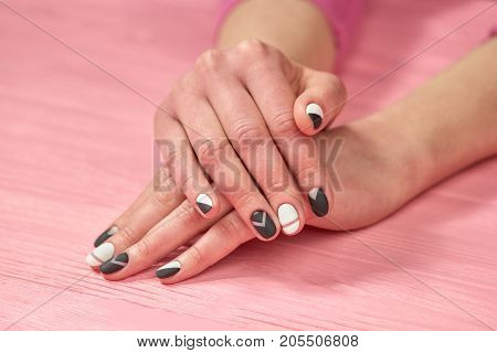 Girls hands with black and white manicure. Female hands with classic colors manicure on salon table. Nail care and treatment.
