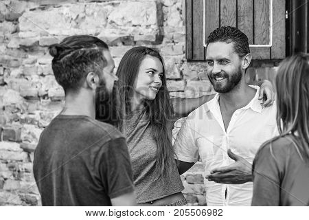 Couple of handsome bearded man with long beard and stylish hair and blonde pretty cute sexy woman or girl embracing and smiling to they friends on summer sunny day on stony wall background