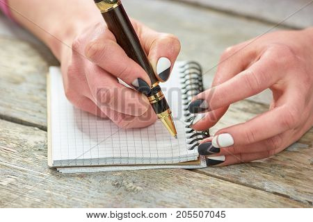Woman with manicured hand writing on notebook. Female hand with modern matte manicure writing a note with a pen on old wooden manicure table.