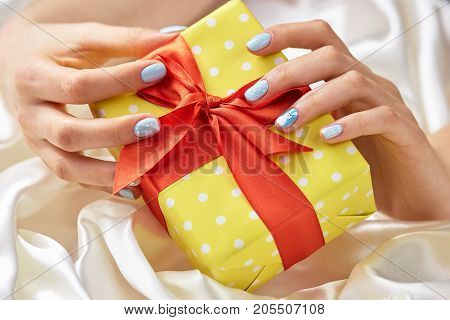 Gift box in female manicured hands. Beautiful yellow gift box in woman hands with gentle winter manicure. Holidays and celebration concept.
