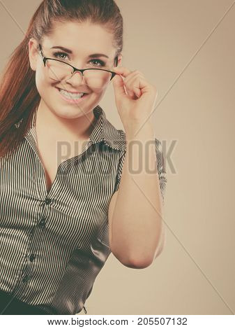 Close up portrait of happy business woman wearing eyeglasses and grey shirt.
