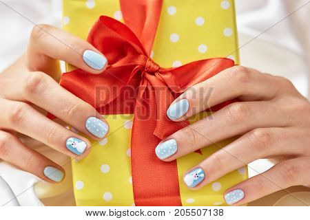Beautiful gift box in female hands. Woman hands with winter manicure holding yellow gift box with red ribbon close up.