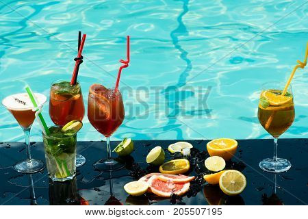 Cocktails at water pool. Drink food and relax. Fruit slice and cocktail glass at bar. Alcoholic beverage and fruit at restaurant. Party and summer vacation.