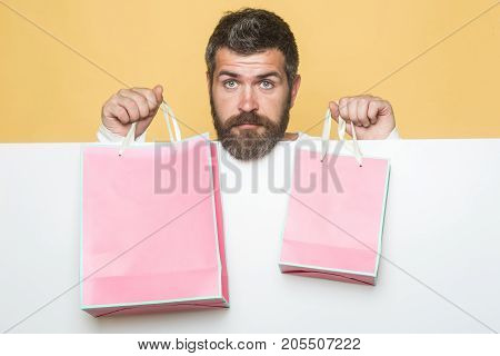 Man with beard with pink shopping bag. Holiday celebration and black friday shopping. Christmas and birthday. Hipster with present package on yellow background. Guy with serious face and gift pack.