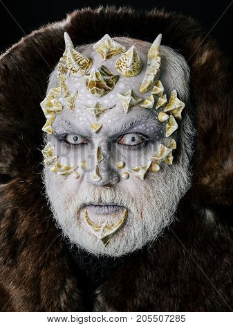 Monster with sharp thorns and warts on face. Demon in fur coat on black background. Horror and fantasy concept. Alien or reptilian makeup. Man with dragon skin and grey beard.