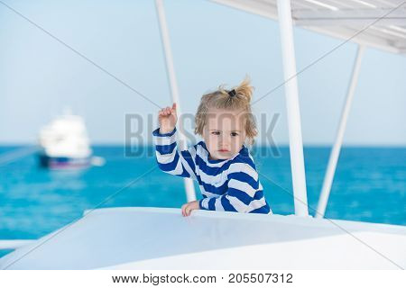 Child in striped shirt looking at blue ocean water. Sea voyage and cruise. Summer trip and vacations. childhood and happiness concept. Boy little kid with cute serious face sailing on white ship.