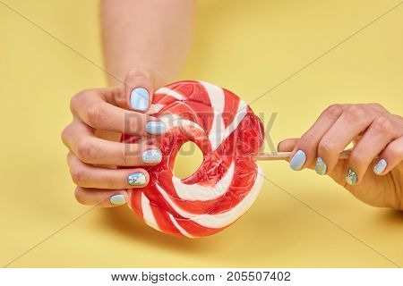 Female manicured hands with lollipop. Woman hands with beautiful manicure holding large colorful lollipop on yellow background.