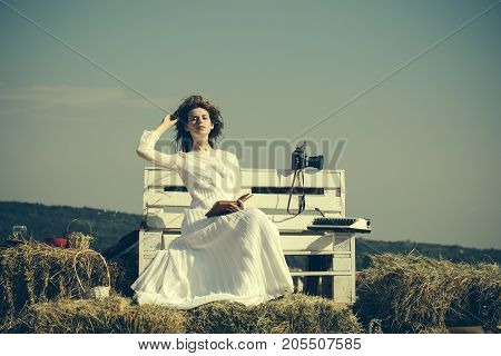 Woman reading book on grey sky vintage filter. Lady in white dress and wreath on sunny day. Summer vacation concept. Education and knowledge. Girl with vintage typewriter and camera on bench.