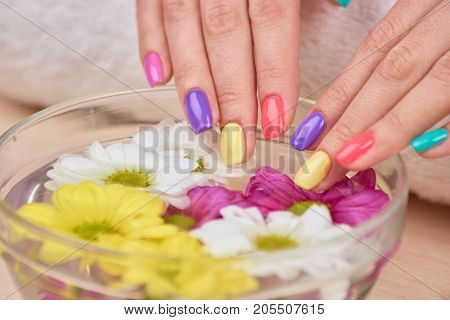 Female hands receiving spa treatment. Young woman beautiful hands with summer colorful nails in bath with aroma water and flowers.