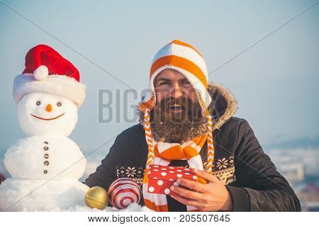 Hipster In Hat Smiling With Snowman In Santa Cap