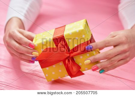 Gift box in female manicured hands. Woman hands with multicolored summer nails holding dotted gift box. Holidays and celebrations concept.