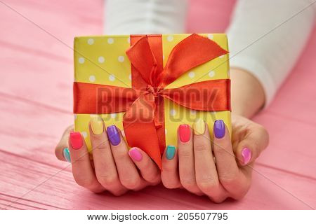 Birthday box in female hands. Yellow dotted gift box with red ribbon in woman manicured hands. Birthday present concept.