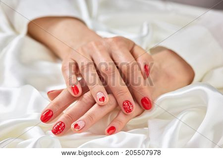 Female romantic design manicure. Young woman well-groomed hands with red patterned nails on white silk. Feminine cleanness and delicacy.