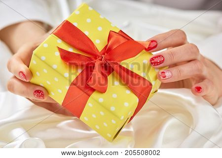 Gift box in gentle female hands. Woman well-groomed hands with romantic manicure holding box with a gift. Concept of holidays and celebrations.