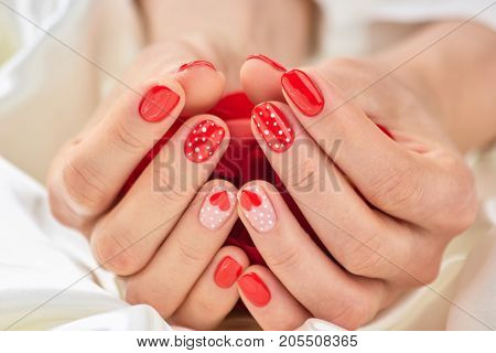 Female manicure on Valentine Day. Female hands with beautiful manicure holding rose petals. Nail design on Valentine Day.