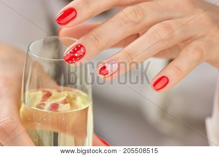 Female manicured hands and champagne. Young woman hands with beautiful polished nails holding glass of champagne. Romance and celebration concept.