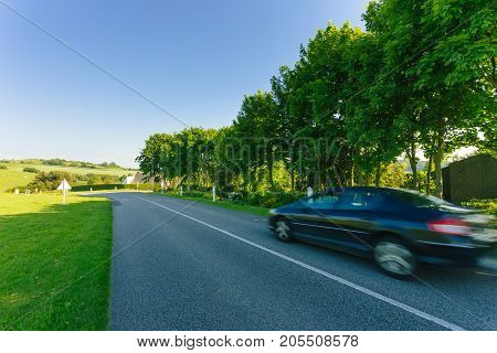 Cars Driving On The Asphalt Road Passing Through Green Agricultural Fields And Forests. Countryside
