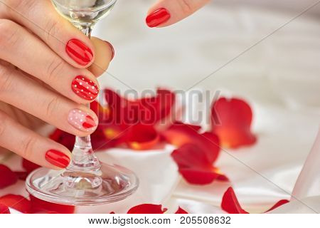 Female red manicure and champagne glass. Beautiful woman hands with gel manicured nails holding a glass of champagne. Romance and celebration concept.