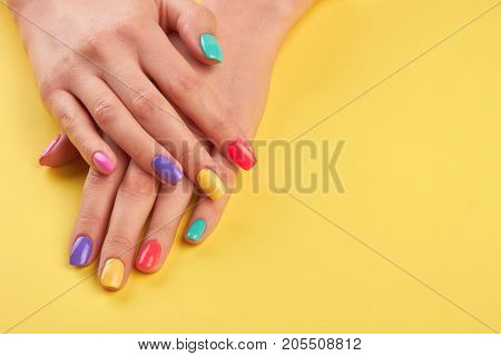 Female hands with summer manicure. Teen girl hands with bright summer manicure on yellow background, copy space.