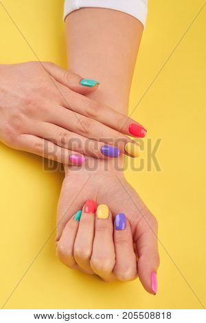 Womans hands with summer colors nails. Multicolor female manicure on yellow summer background.