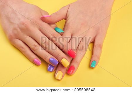 Woman nails painted in different colors. Stylish colorful nails and on a bright background. Nail care studio.