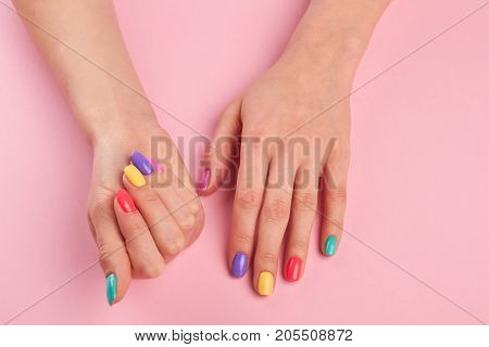Pastel manicure on female hands. Young woman hands with colorful nail polish on pink table, top view. Nail salon and spa.