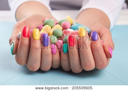 Colorful candies in womans hands. Female hands with summer colors manicure holding bright tasty candies. Many candies in woman hands.