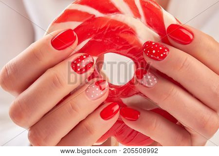 Large lollipop in manicured hands. Woman hands with red manicure holding red and white tasty lollipop.