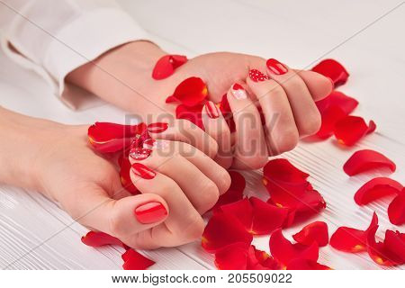Beautiful red manicure and rose petals. Female hands with red patterned manicue holding rose petals on white wooden background.