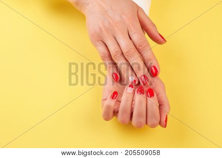 Female hands with fresh stylish manicure. Woman manicured hands isolated on yellow background. Cute nails art for Valentines Day.