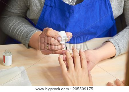 Manicurist applying colorless varnish. Female manicurist doing manicure to client in nails salon. Nails and skin treatment.