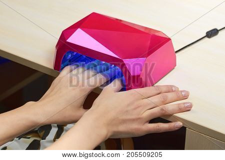 Client drying gel coat on nails. Client in manicure salon dryes gel polished nails in UV light. Drying nails in special machine.