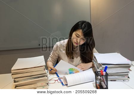Asian manager reading reports in meeting room