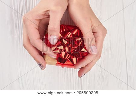 Little gift box in female hands. Beautiful small box with gift in woman manicured hands, top view. Holidays and celebrations concept.