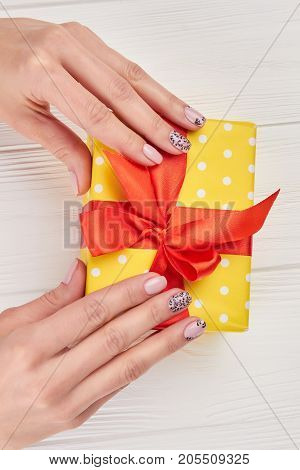 Female manicured hands and gift box. Yellow gift box with red bow in gentle female hands, top view. Festive concept.