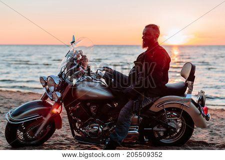 Biker and motorcycle. Outdoors photo. horizontal shot