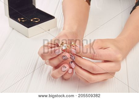 Female hands holding golden jewelry. Female hands with manicure and jewelry. Many beautiful gold rings in woman manicured hands.