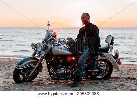 Biker on the beach at sunset. horizontal shot